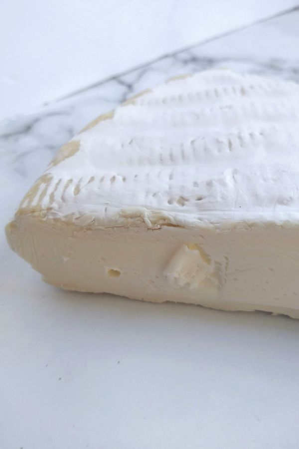 A side shot of Brie cheese sitting on a counter