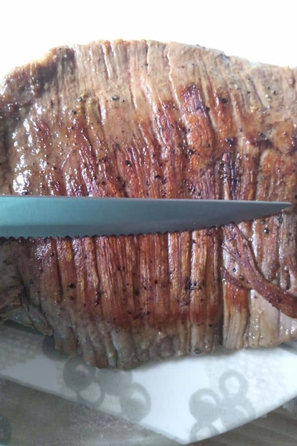 A close up of a flank steak that shows the grain with a knife next to it, demonstrating how to slice against the grain.