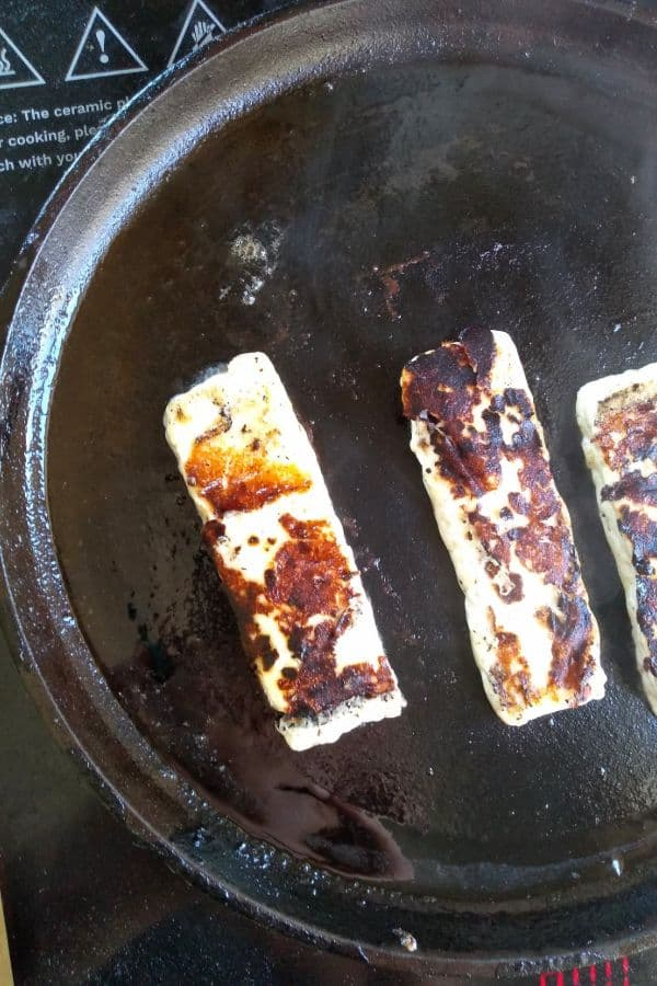 Panela cheese being fried on a cast iron pan
