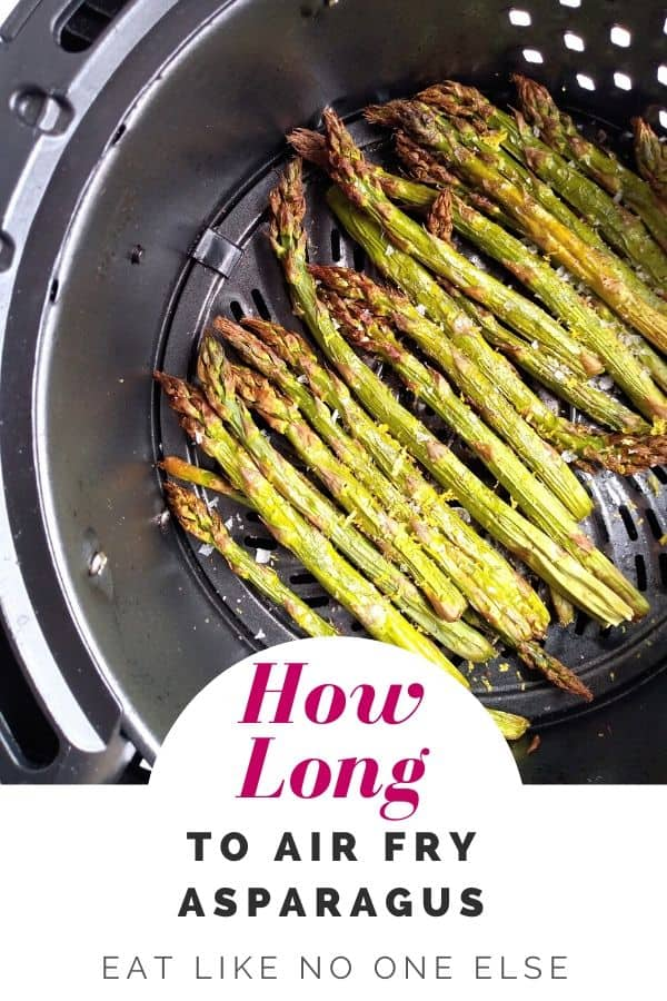 Asparagus that is done sitting inside of an air fryer basket
