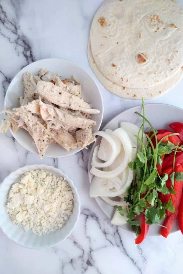 All the ingredients for turkey fajitas - leftover turkey, peppers, Cotija cheese, onions, cilantro, and flour tortillas