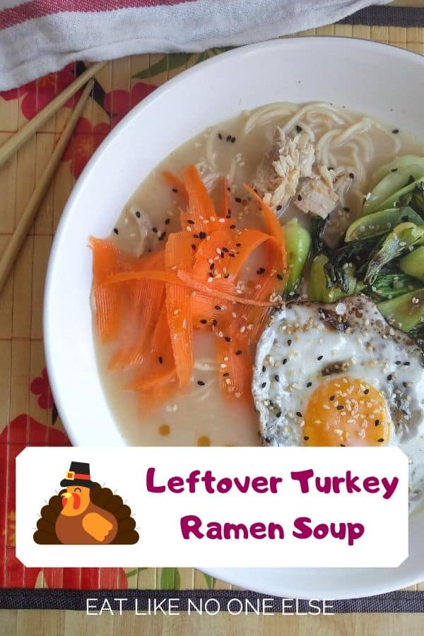 "A bowl of turkey ramen soup with bok choy, a fried egg, sesame oil, and carrots is in a white bowl with the words ""Leftover turkey ramen soup"" over top."
