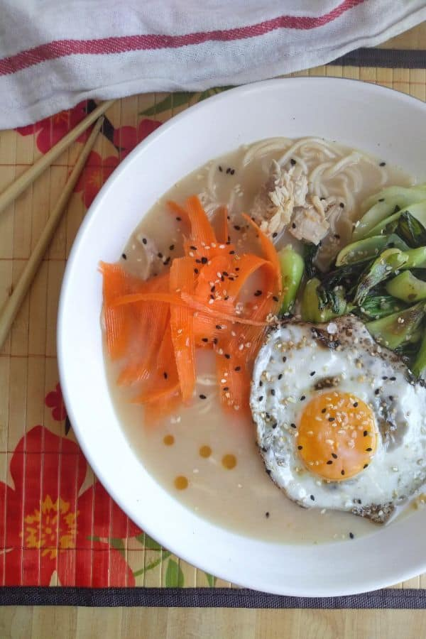 A bowl of turkey ramen soup with bok choy, a fried egg, sesame oil, and carrots is in a white bowl with the words ""