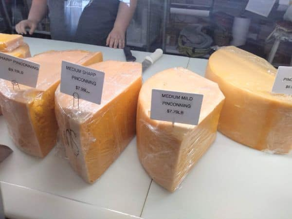 A store case with large cuts of Pinconning cheese in medium mild, medium sharp and sharp