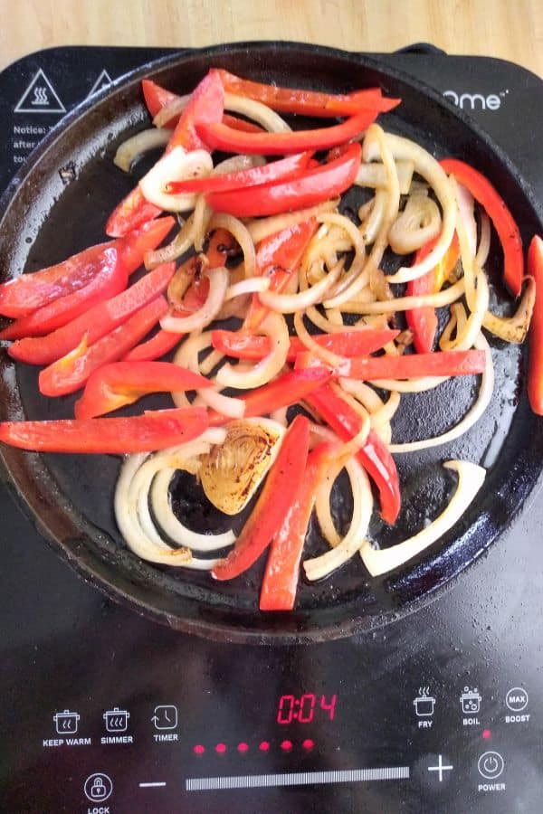Onions and peppers on a cast iron skillet cooked on an induction cooktop