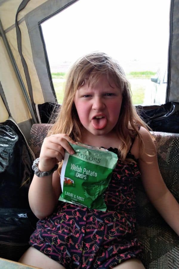 The author's daughter holding up a bag of Taylors Welsh Lamb and Mint chips. She is making a yucky face.
