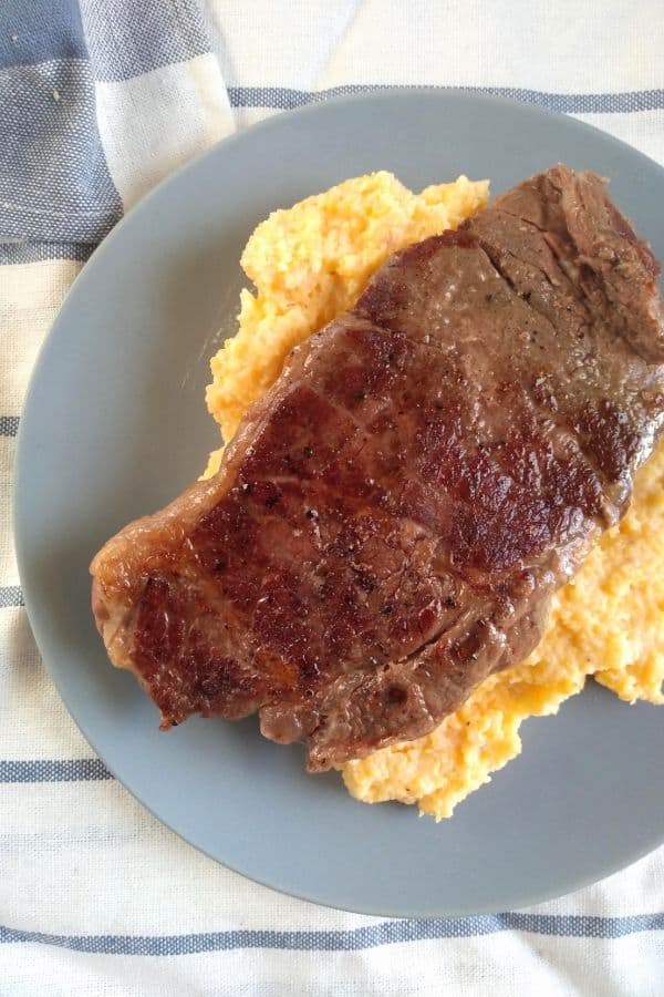 A sous vide and seared chuck blade steak served on top of grits on a bluish gray plate.