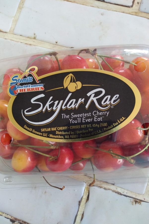 "Skylar Rae cherries in a plastic container with the tag line ""the Sweetest Cherry You'll Ever Eat"""