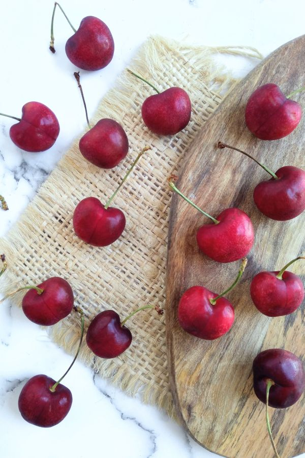 Audra Rose cherries sitting on a cutting board with a burlap cutout and a white title underneath
