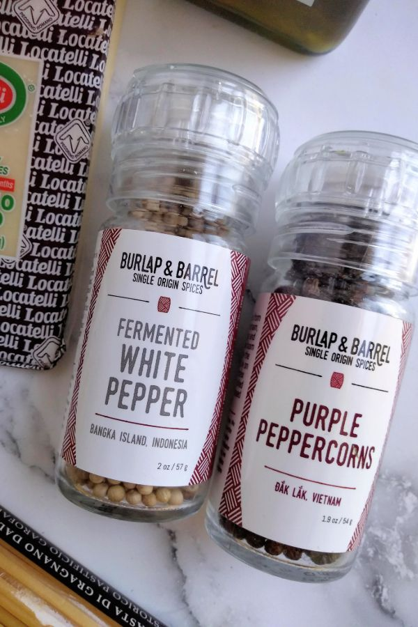Burlap & Barrel Fermented white pepper and purple peppercorns in glass containers with a grinder top