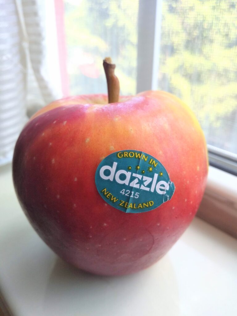 A single Dazzle apple sitting on a shelf in a window sill