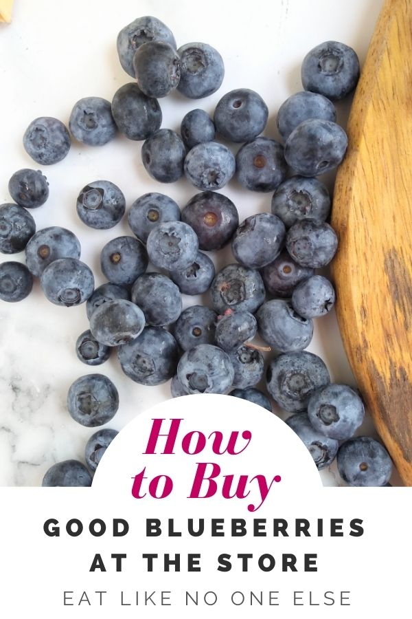 """Blueberries on a white background with a wood board to the right with the words """"How to Buy Good Blueberries at the Store"""" at the bottom"""