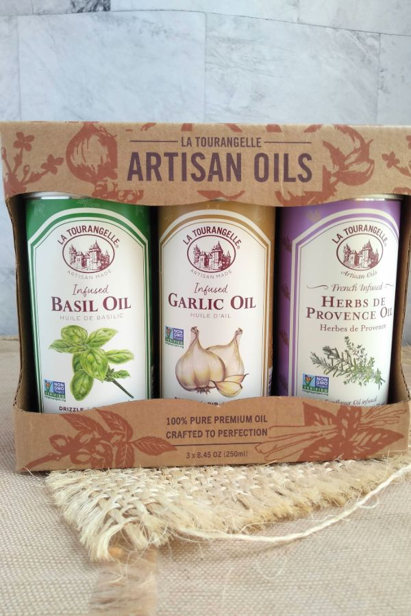 Bottles of La Tourangelle Artisan Oils - Infused Basil Oil, Infused garlic Oil, Herbs de Provence Oil inside a three pack box.