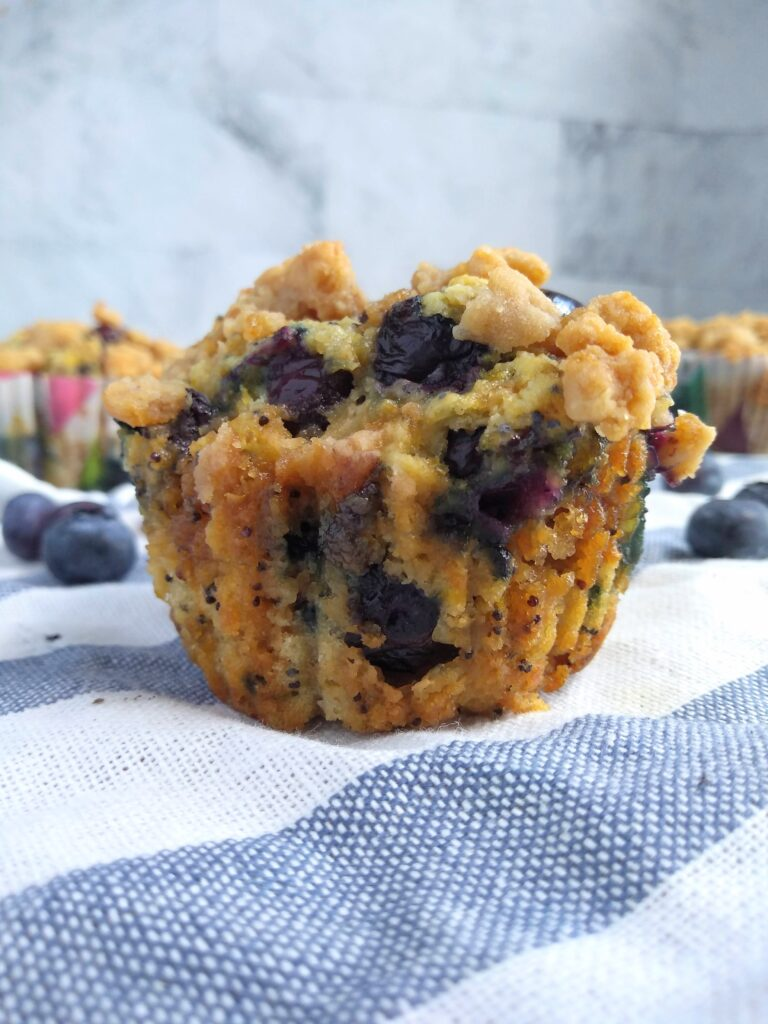A blueberry sour cream muffins with poppy seed and lemon sitting on a blue and white striped towel with additional muffins in the background.