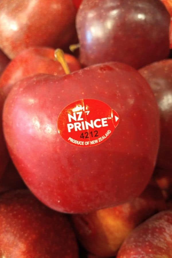 A single NZ Prince apple is in the center and it's sitting on a display of more NZ Prince apples in a grocery store
