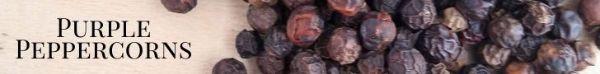 purple peppercorns on a wood board