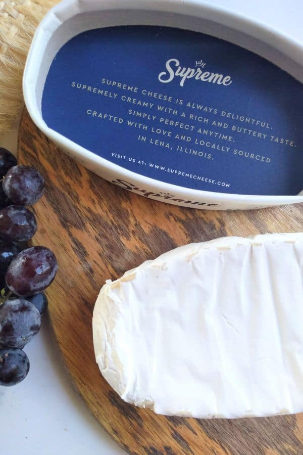 Supreme brand Brie cheese sitting on a cutting board with some grapes with the lid of the cheese upside down