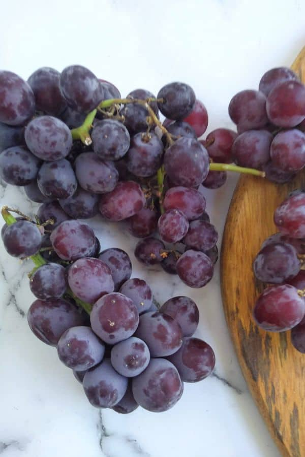 Candy snaps grapes sitting mostly on a white surface but also on a wood cutting board