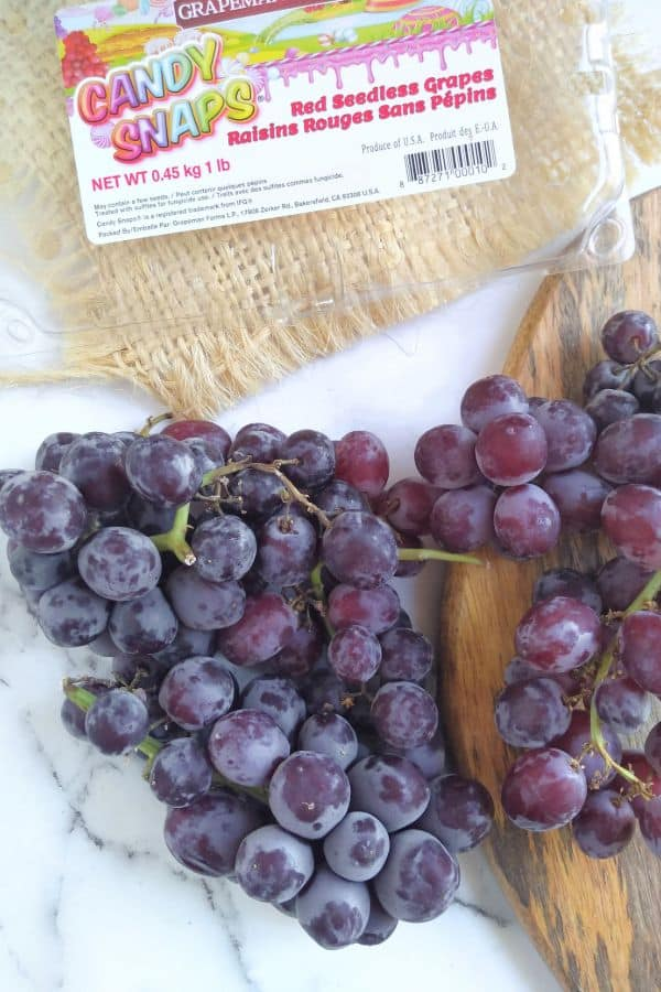 Candy Snaps grapes in bunches sitting on a white surface with a wood board next to it and the empty package as the top