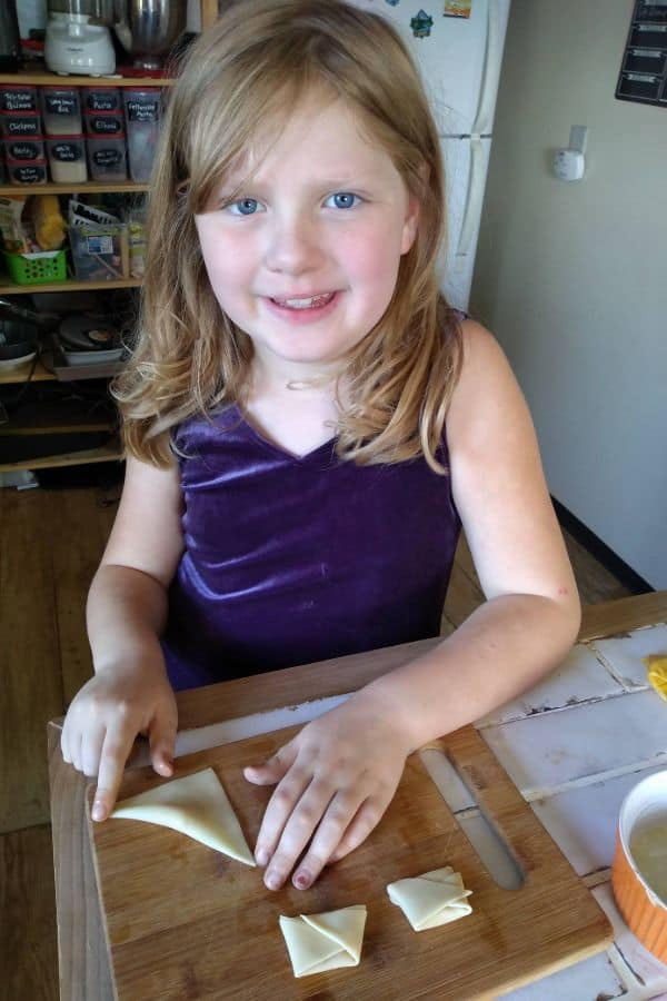A young girl folding wontons for tortellini in the kitchen.