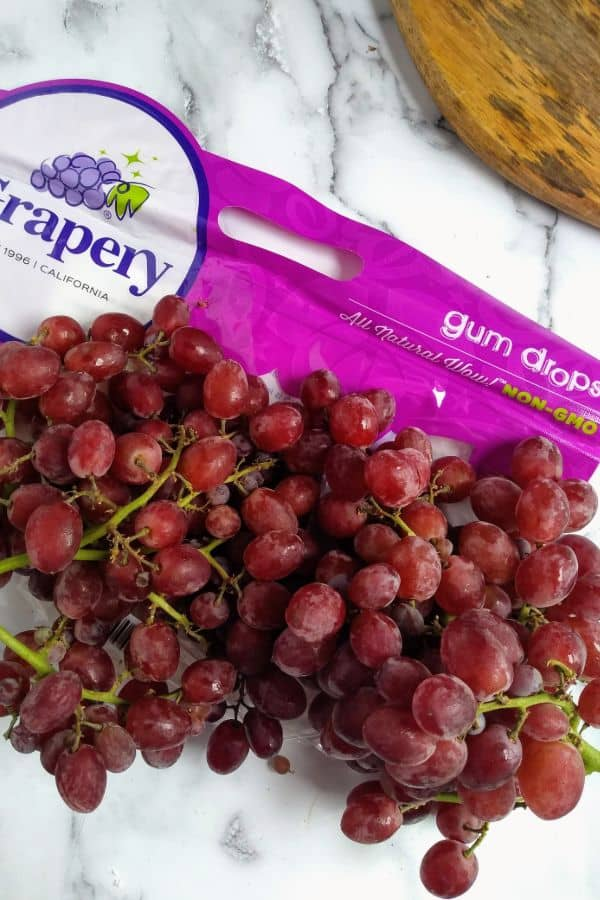 Candy Snaps Gum Drops grapes are sitting on a counter in bunches with the bag in the background