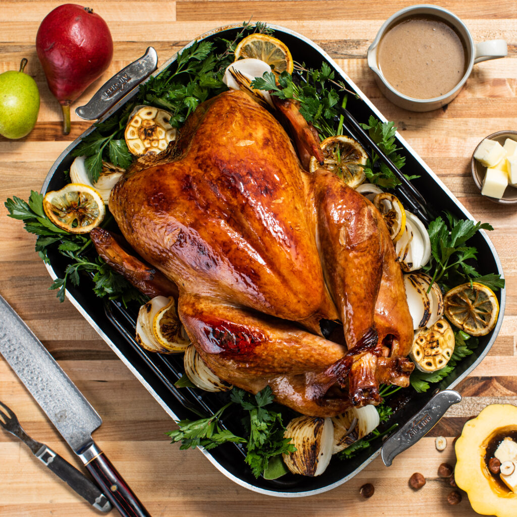 A cooked turkey sitting on a platter with lemons, parsley, and garlic. The platter is one top of a wooden board with pears, gravy, cut open squash, a fork, a knife and butter nearby.