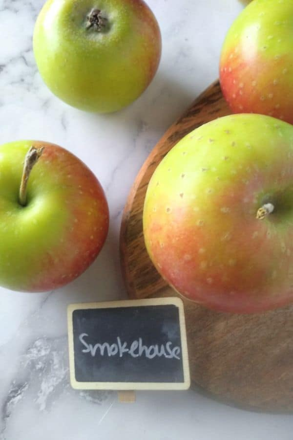 Smokehouse apples sitting on a cuttingsboard and a white backdrop