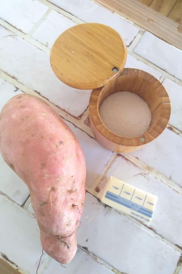 A large sweet potato, a half stick of butter, and a container of kosher salt are sitting on a white counter top.