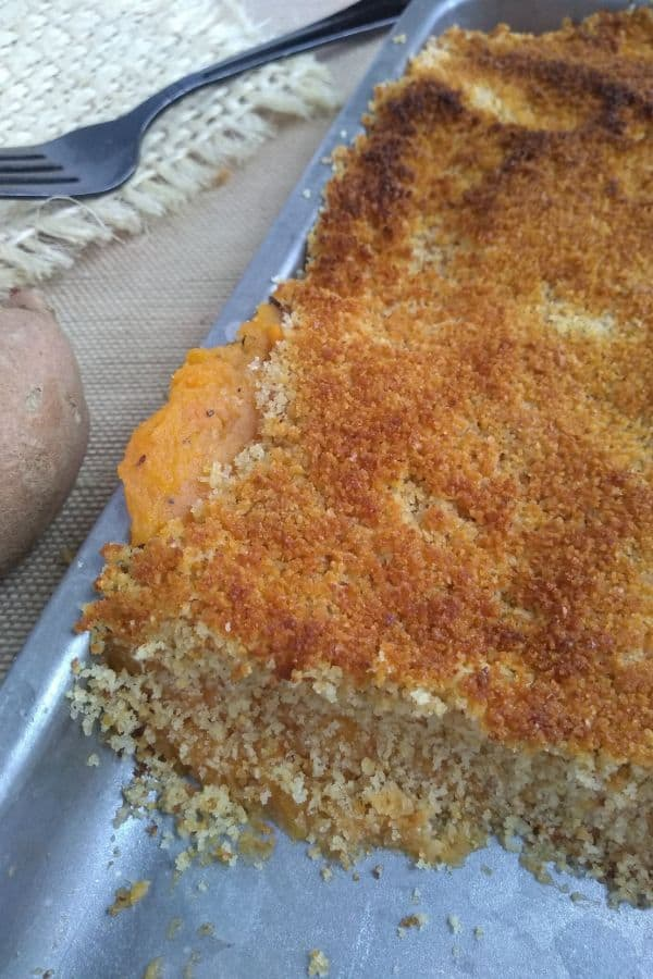 Sweet potatoes are spread onto a mini sheet pan topped with bread crumbs. The pan has just come out of the oven and the bread crumbs are toasted