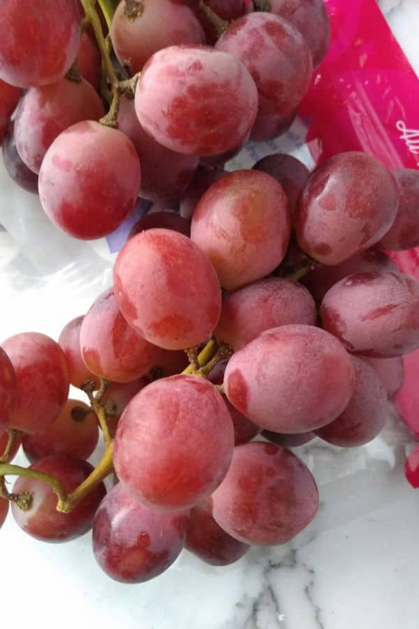 A close up view of Grapery Red Limited grapes in a bunch on top of the bag
