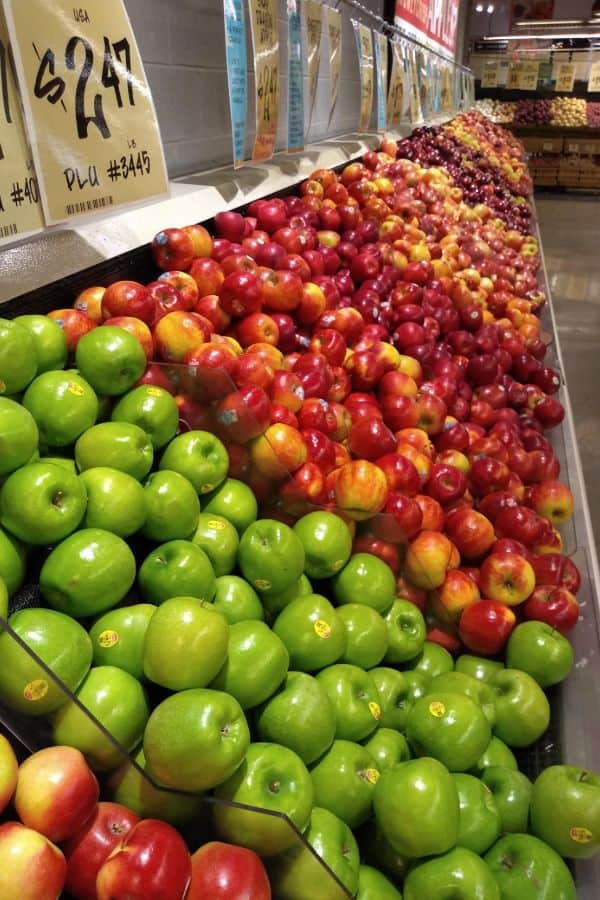 A display of several different types of apples of various colors and shapes.