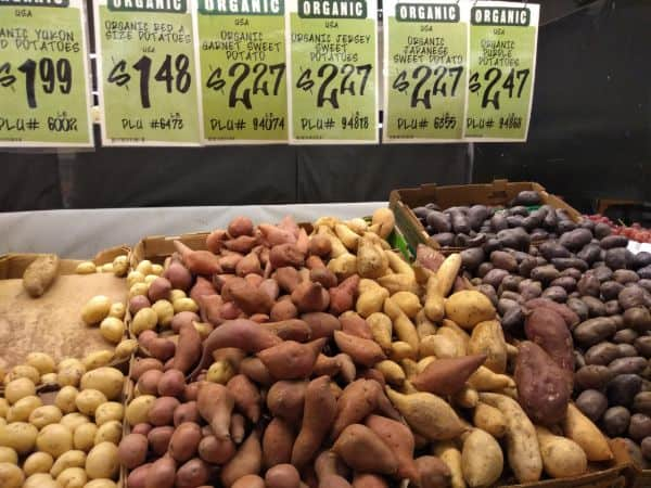 A store display featuring red, Garnet sweet, Jersey sweet, Japanese swet, and organic purple potatoes.
