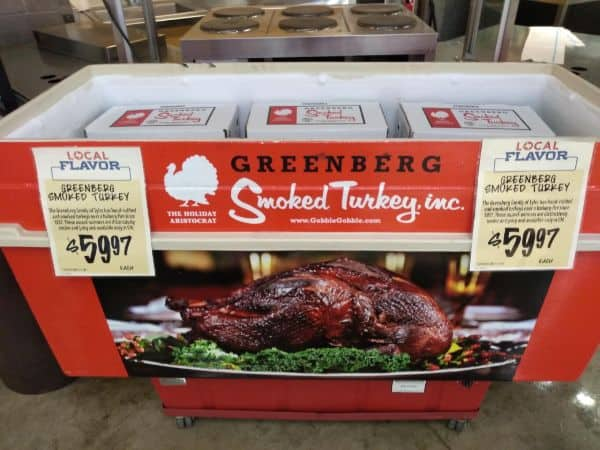 A display for Greenberg Smoked Turkeys with boxes of turkey inside the display and a smoked turkey picture on the front. The price sign says they are $59.97 each.