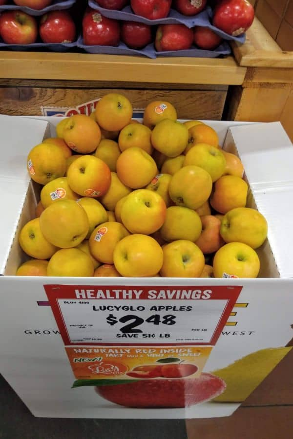 A box display of yellow skinned Lucy Glo apples