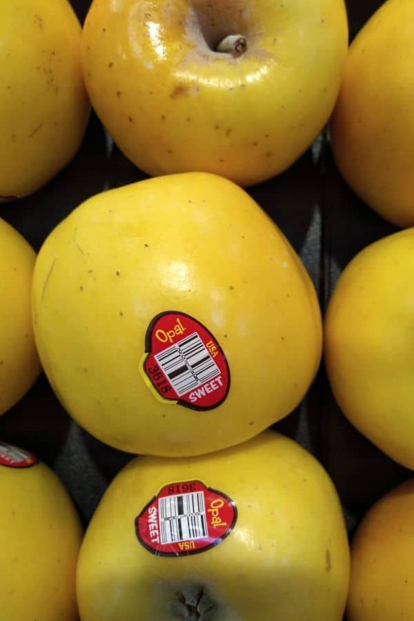 A display of Opal apples at Kroger store. The apples have a red PLU sticker on them that says Opal Sweet.