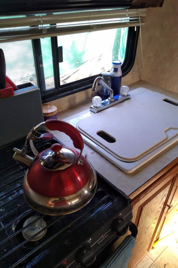 The kitchen inside a travel trailer with the sink covered with a cutting board.