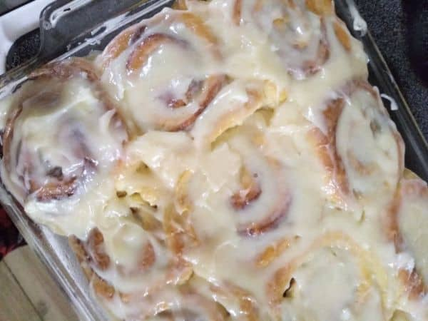 A glass pan filled with cinnamon rolls that have been frosted.