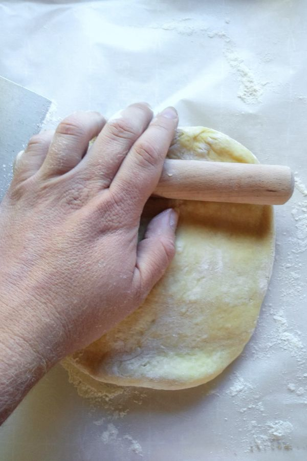 A hand is shown with a small rolling pin rolling out dough on top of a parchment lined cutting board.
