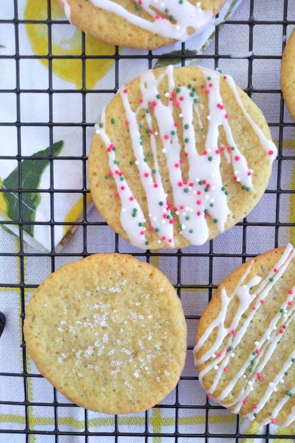 Meyer lemon anise cookies on a black cooling with a lemon towel underneath. Half the cookies have a lemon icing and the other half have coarse sugar on them.