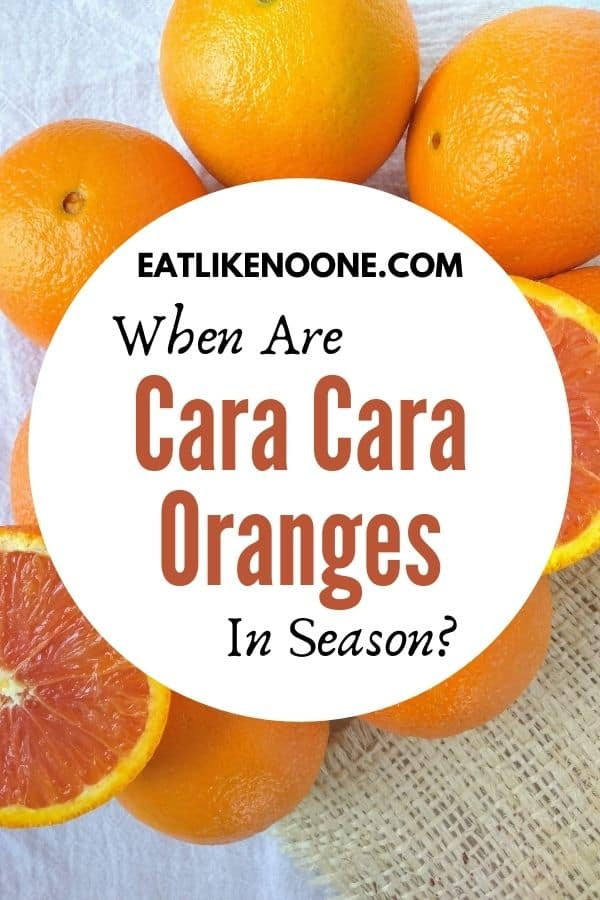 """The words """"When are Cara Cara Oranges"""" in season appear in a white circle in front of orangs laying on a counter top."""