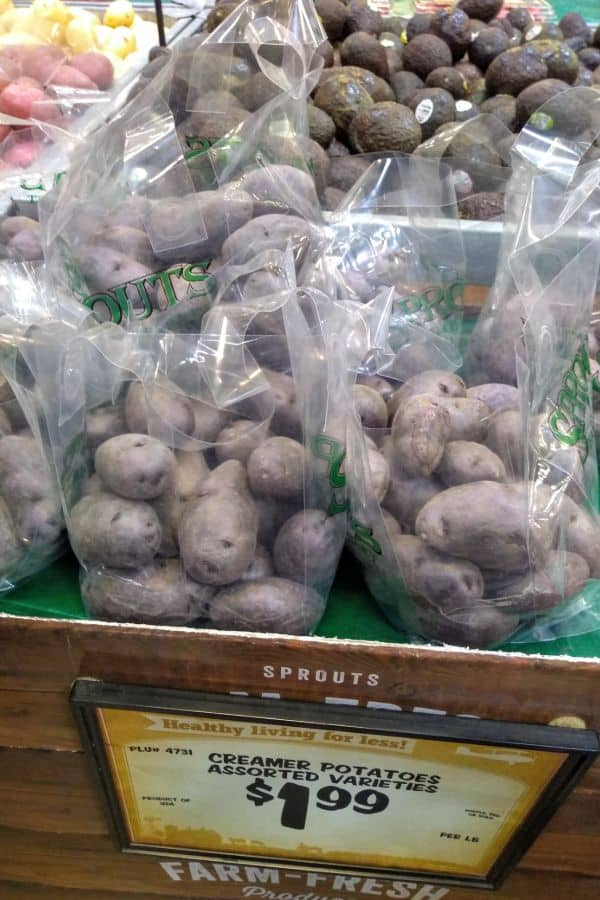Purple potatoes in see through bags on a display at a Sprouts store. A sign says they are $1.99 per lb.