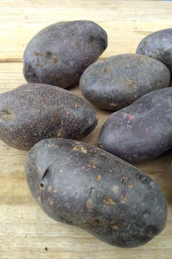 Purple potatoes on a wood board.