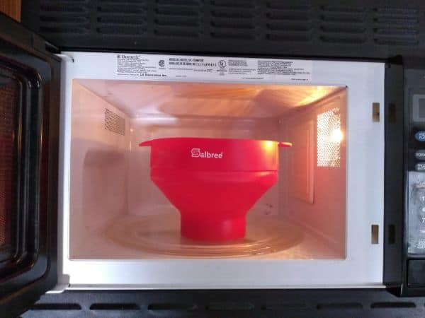 A red Salbree Silicone popcorn popper inside a black microwave.