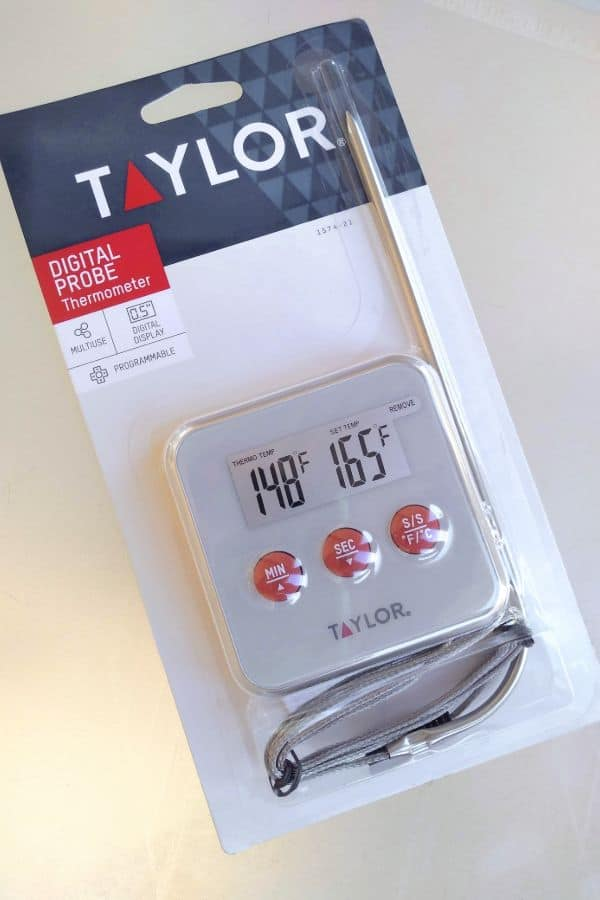 A Taylor Digital Probe thermometer in it's packaging from the store on a white surface.