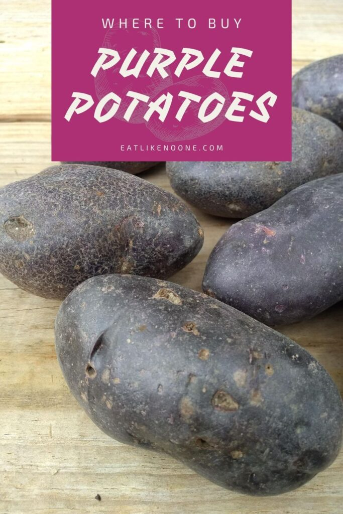 """Purple potatoes sitting on a wood picnic table with the words """"Where to buy Purple Potatoes"""" at the top."""