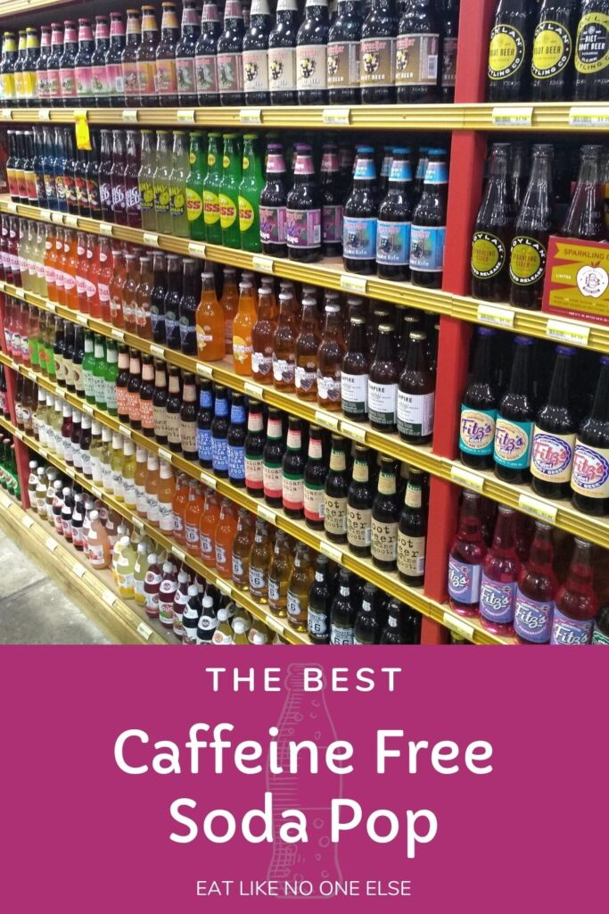 "A display of glass bottled soda in a grocery store with the words ""the Best Caffeine Free Soda Pop"" at the bottom."