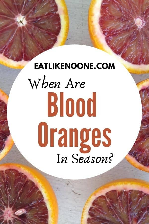 "The words ""When are Blood Oranges in Season"" appear in a white circle overtop blood oranges that have been cut in half."