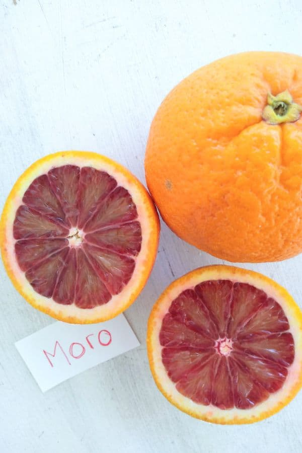 A sliced open Moro blood orange on a white wood background.