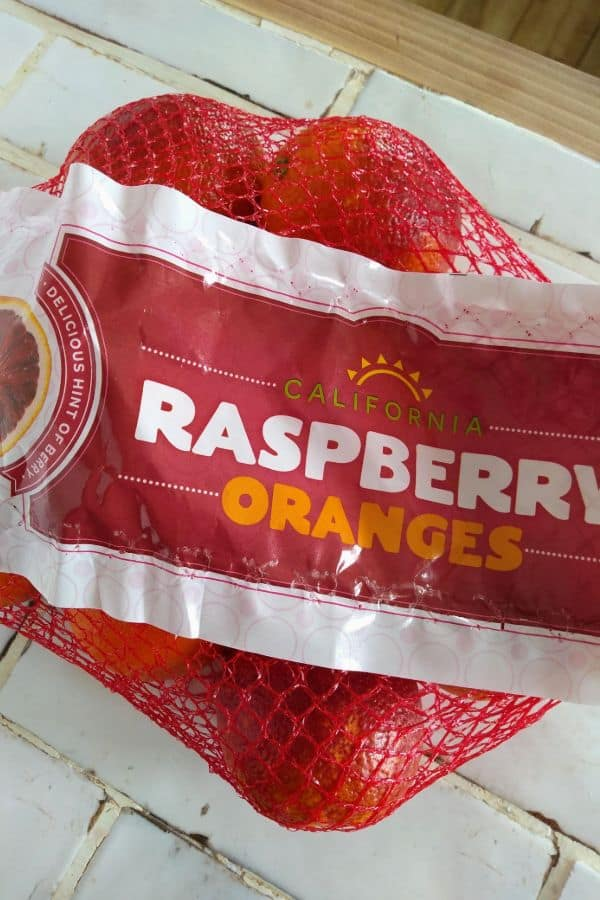A bag of raspberry oranges sitting on a white counter.