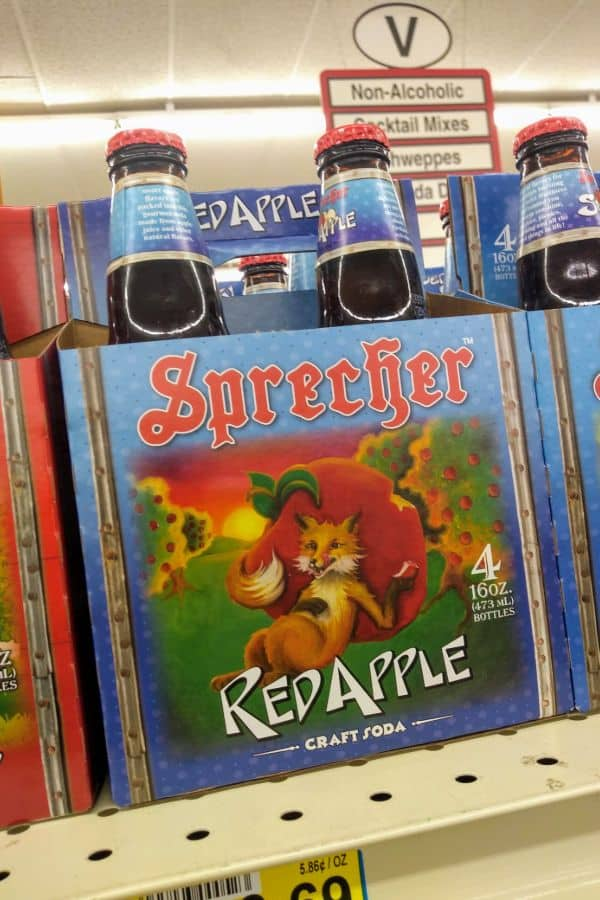 A 4 pack of Sprecher Red Apple soda on a grocery store shelf.